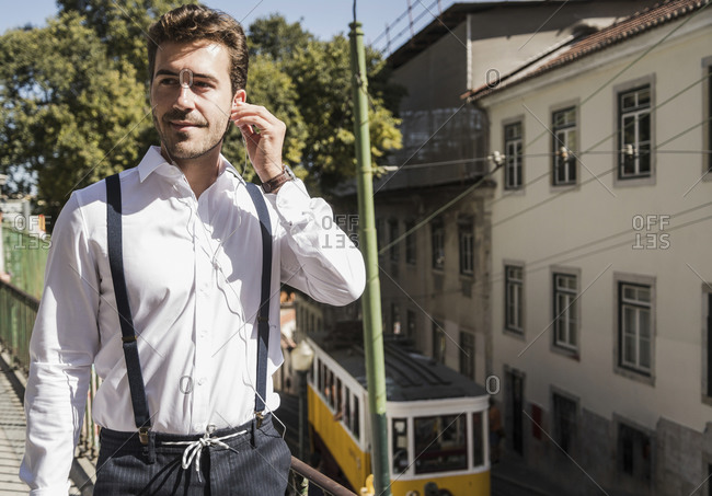 Young man with earbuds in the city- Lisbon- Portugal