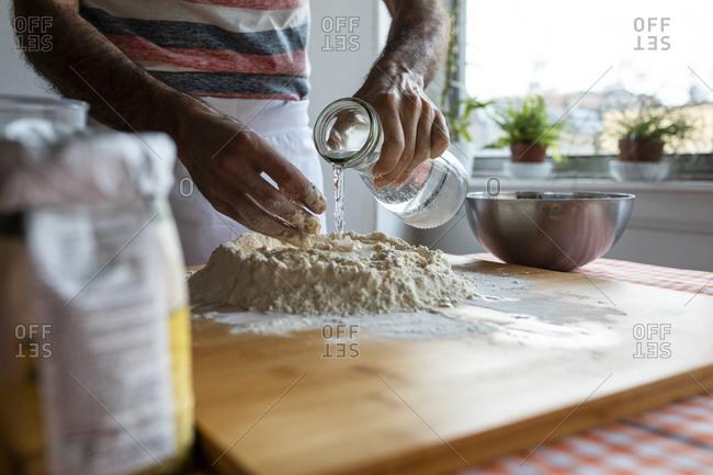 Crop view of man in kitchen preparing dough
