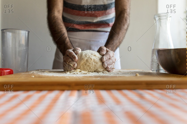 Crop view of man kneading dough