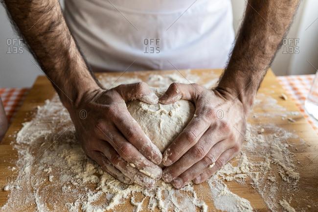 Man's hands shaping heart on dough ball