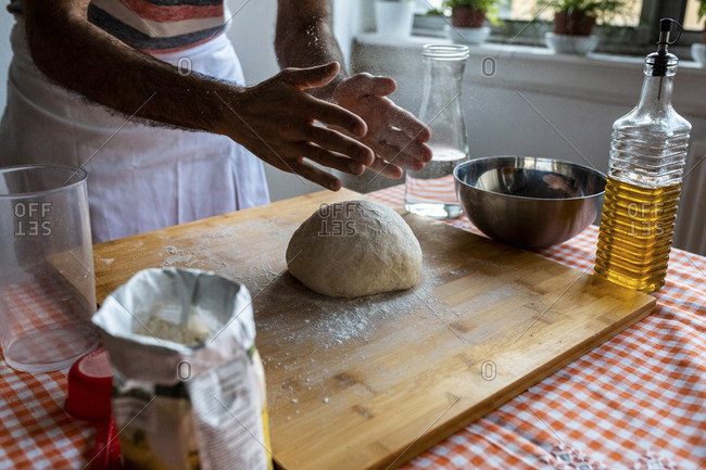 Crop view of man spreading flour on dough ball in the kitchen