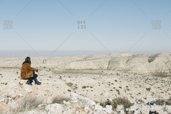 Full length of woman sitting on rocks while looking at desert landscape against clear blue sky
