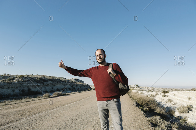 Man gesturing while hitchhiking on roadside at desert against clear blue sky
