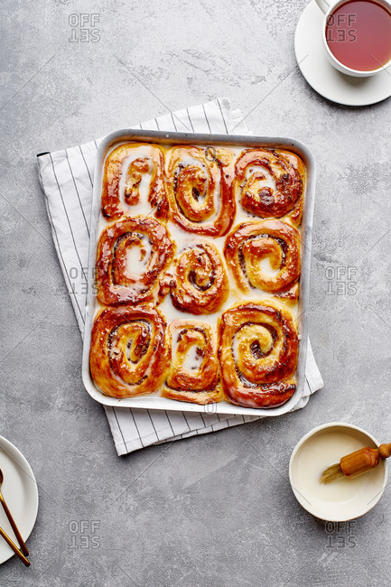 Cinnamon buns on a baking tray with date filling and cream glazing