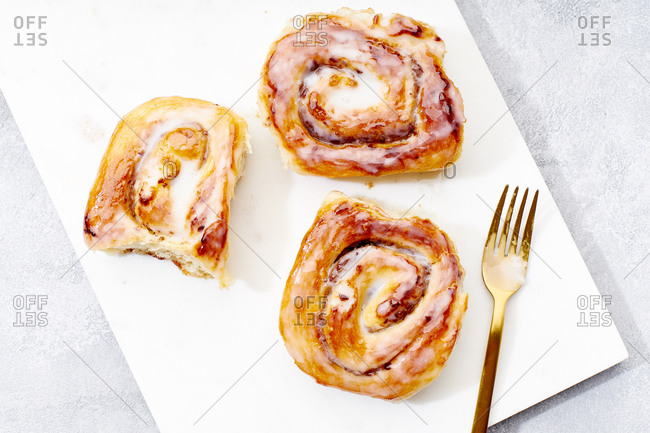 Cinnamon buns on a marble cutting board with date filling and cream glazing