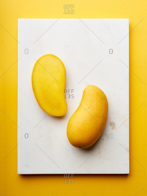 Sliced yellow mango on marble cutting board and yellow background. Top view