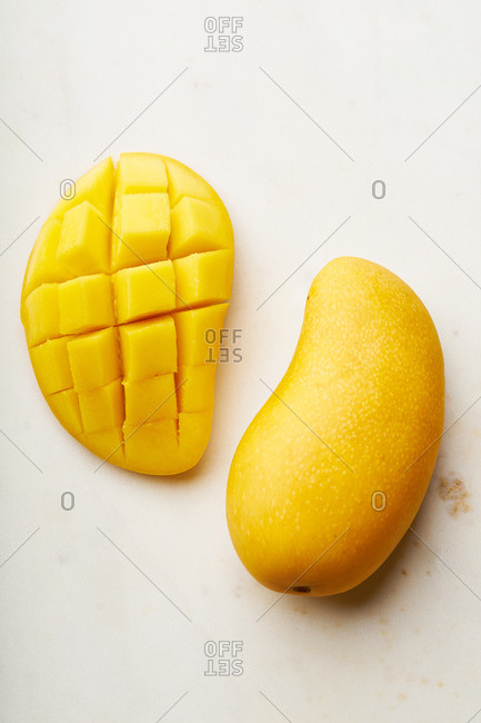 Top view image of sliced yellow mango on marble cutting board.