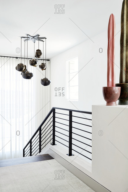 Paradise Valley, Arizona - July 10, 2019: Unique light fixture hanging over two-story open staircase in a modern home