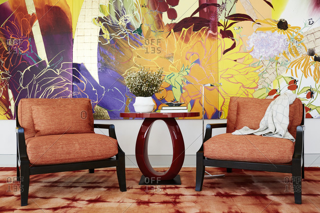 Paradise Valley, Arizona - July 10, 2019: Two cushioned chairs beside red side table in front of large colorful painting