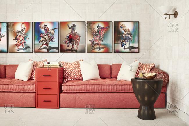 Paradise Valley, Arizona - July 10, 2019: Rodeo artwork above red-orange sofas