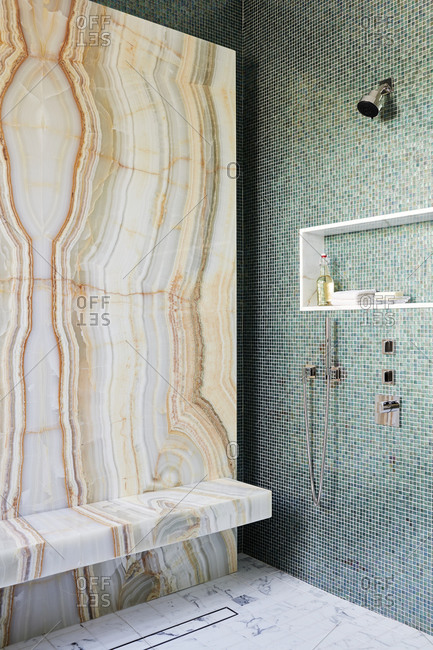 Paradise Valley, Arizona - July 11, 2019: Beautiful stone wall in shower contrasting a mosaic tile wall