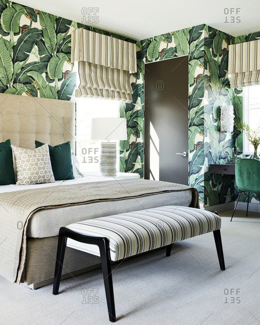Paradise Valley, Arizona - July 11, 2019: Bedroom interior with green accents and leafy wallpaper