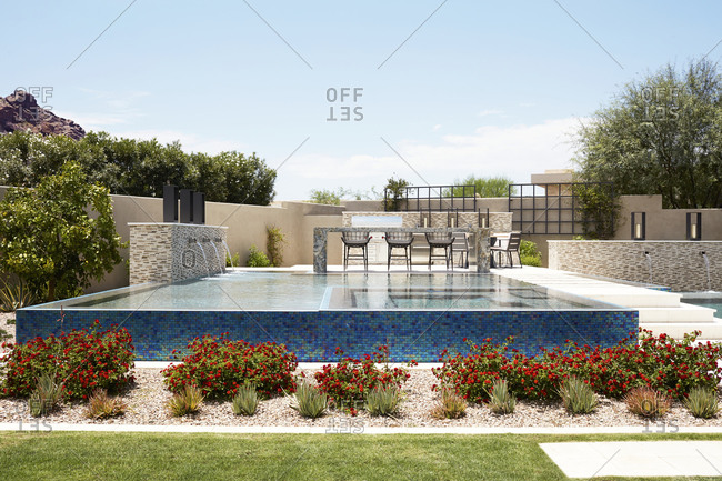 Paradise Valley, Arizona - July 10, 2019: Backyard with blue tile infinity pool