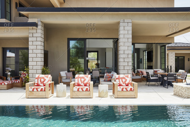 Paradise Valley, Arizona - July 10, 2019: Red pattern lounge chairs beside pool in the backyard of an upscale home