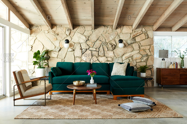 June 1, 2020: Living room interior with stone accent wall and midcentury modern furniture