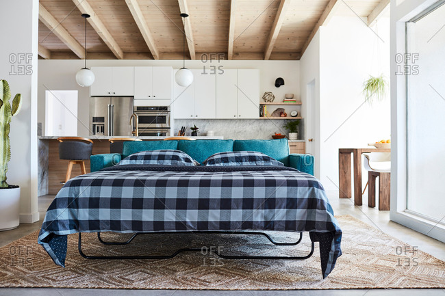 Pullout sofa with blue checkered blanket in modern home