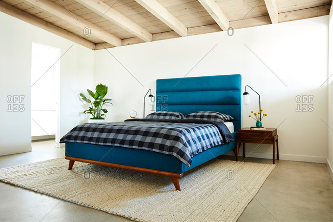 Bedroom interior with a blue headboard and checkered bed set
