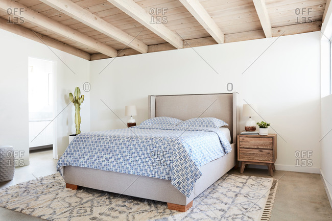 Bedroom interior with a gray headboard and blue patterned bed set