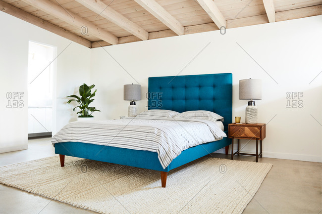 Bedroom interior with a bright blue headboard and blue striped bed set