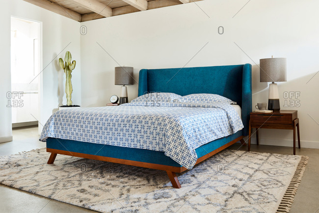 Bedroom interior with a bright blue headboard and blue patterned bed set