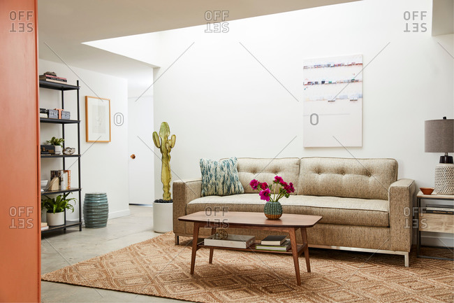 June 1, 2020: Modern home interior with tan midcentury modern sofa
