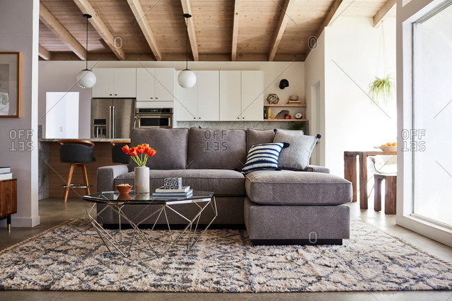 June 1, 2020: Gray sofa with chase in a modern living room with exposed beam ceilings