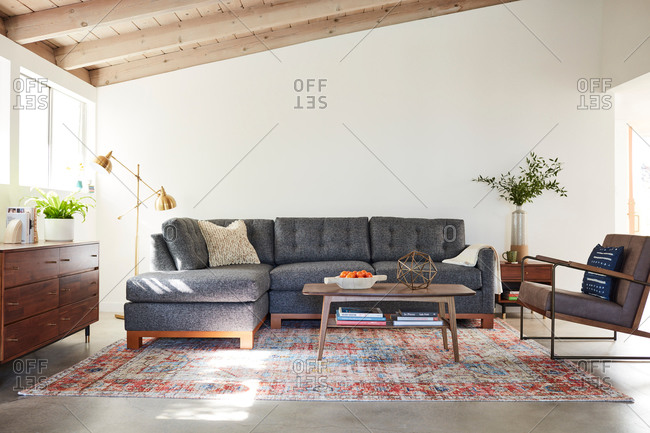 February 12, 2020: Gray sectional sofa in a living room with exposed beam ceilings