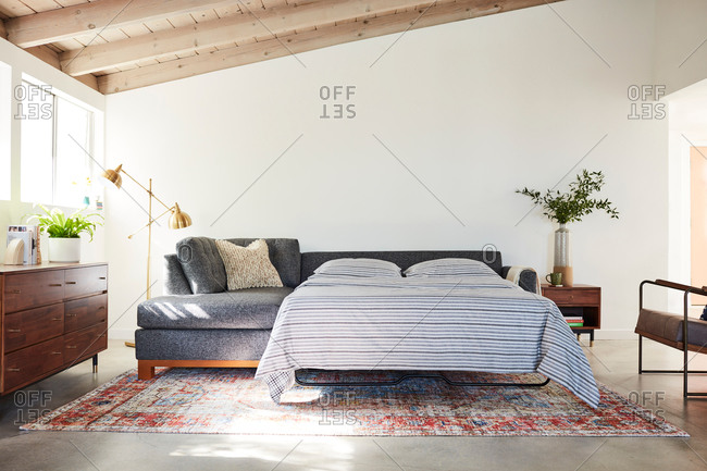 June 1, 2020: Gray sectional sofa with pullout bed in a living room with exposed beam ceilings