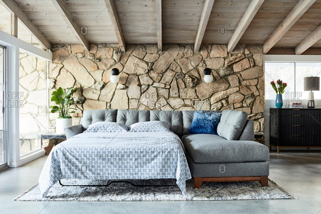 June 1, 2020: Gray sectional sofa with pullout bed in a living room with stone wall