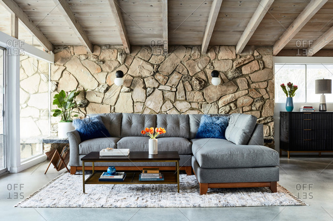 June 1, 2020: Gray sectional sofa in a living room with exposed beam ceilings and stone wall