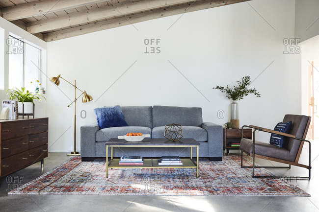 January 31, 2020: Gray sofa and chair in a living room with exposed beam ceiling