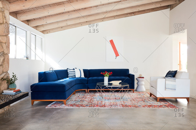 June 1, 2020: Blue velvet sectional sofa in a room with exposed beam ceiling