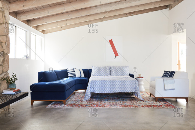 March 30, 2020: Blue velvet sectional sofa with pullout-bed in a room with exposed beam ceiling