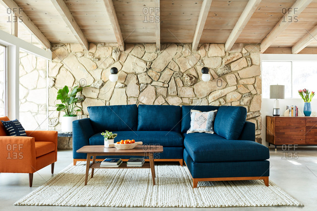 June 1, 2020: Blue sectional sofa in a room with exposed beam ceiling and stone wall
