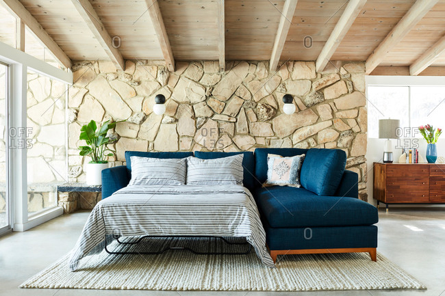 June 1, 2020: Blue sectional sofa with pullout bed in a room with exposed beam ceiling and stone wall