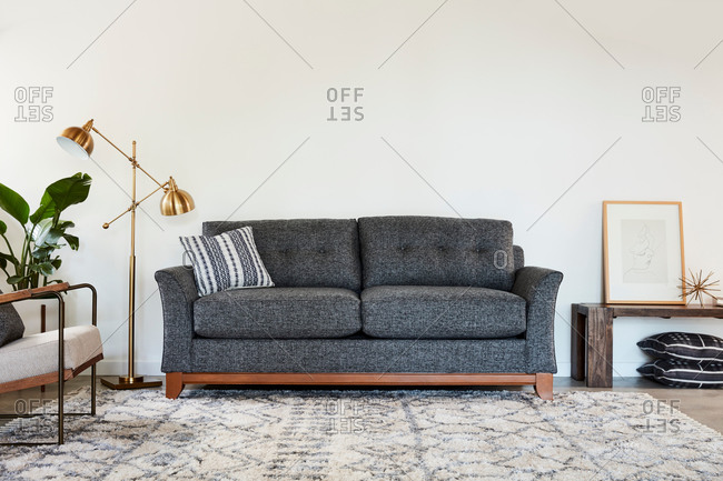 June 1, 2020: Gray and wooden sofa beside a gold lamp