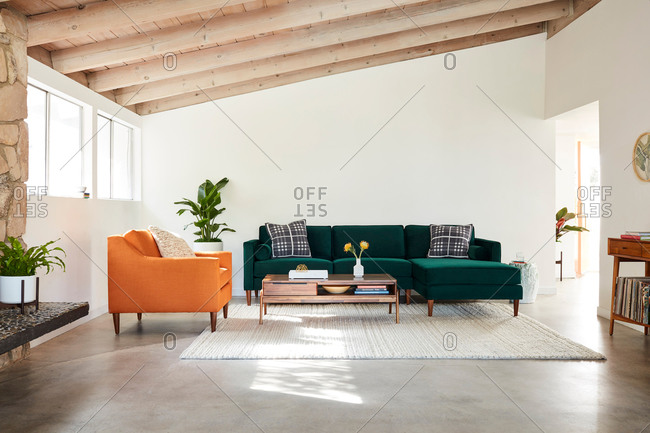 June 1, 2020: Green velvet sectional sofa and orange chair in a room with exposed beam ceiling