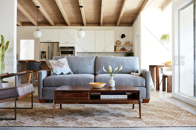 June 1, 2020: Gray couch and midcentury modern coffee table in an open concept home with exposed beam ceilings