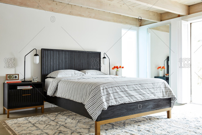 June 1, 2020: Bedroom interior with a black headboard and striped bed set