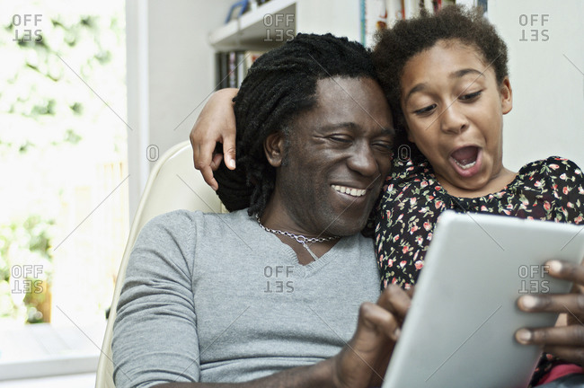 Man and daughter using a digital tablet, sharing the screen.