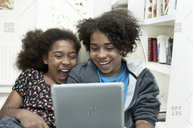 Two children online, sharing a laptop computer laughing.