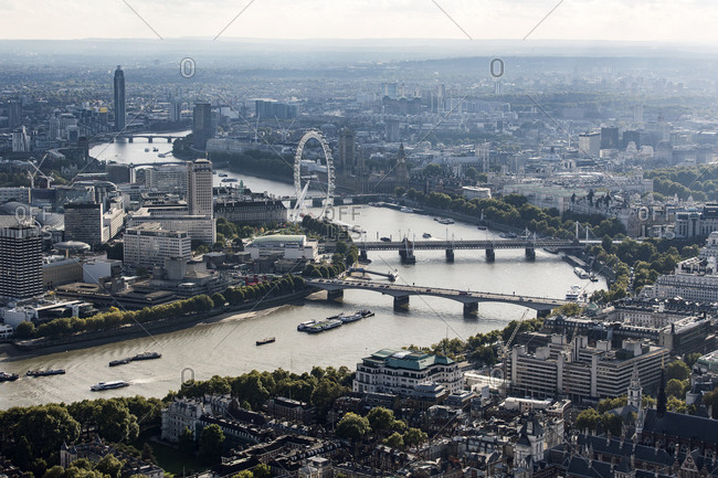 London, United Kingdom - May 29, 2020: Aerial view of the City of London and the River Thames towards the west, with landmarks like the London Eye, and rooftops.
