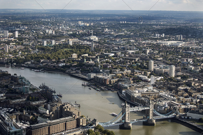 Aerial cityscape of London at Tower Bridge and the River Thames, and landmarks on the river banks.