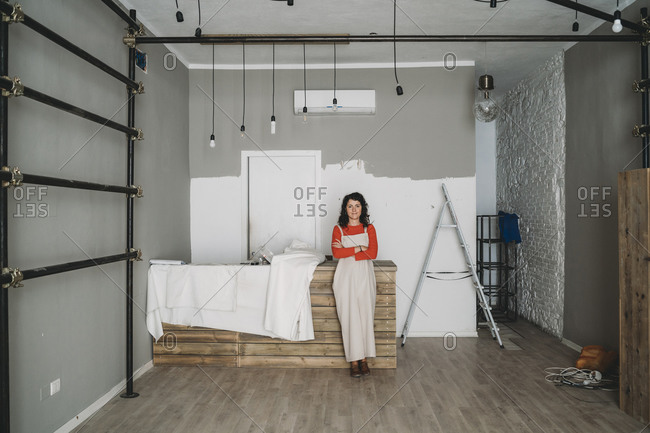 Mid adult woman leaning against table in her new shop, full length portrait