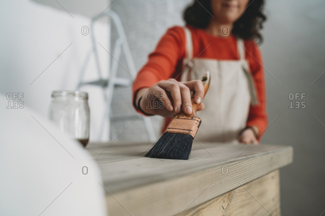 Mid adult woman varnishing wooden table in her new shop, cropped shallow focus