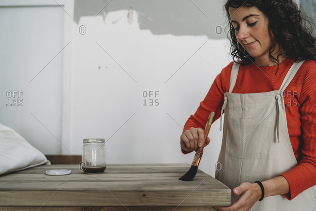 Mid adult woman varnishing wooden table in her new shop