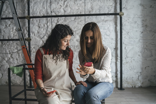 Two mid adult women looking at smartphone in their new shop