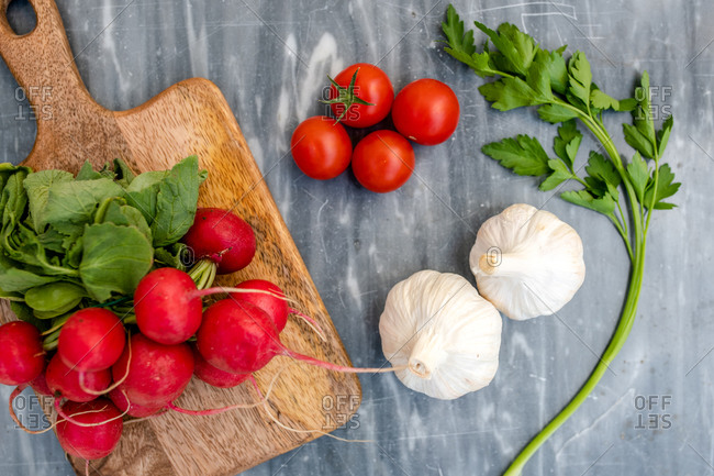 High angle close up of freshly picked radishes, garlic and flat leaf parsley and wooden chopping board on grey marble.