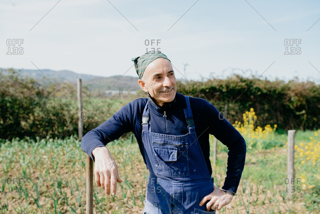 Smiling man wearing dungarees and bandana standing in vegetable garden, leaning on wooden pole.