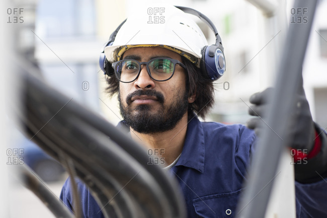 Bearded man wearing eyeglasses and white hard hat working on construction site.